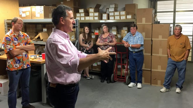 Former U.S. Sen. Rick Santorum speaks Thursday at Frog Legs, a business in Ottumwa that makes components for wheelchairs. The firm is owned by state Sen. Mark Chelgren, R-Ottumwa, who is standing to the left of Santorum.