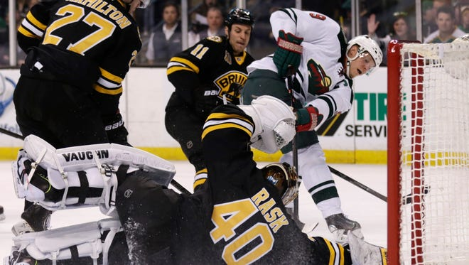 Boston Bruins goalie Tuukka Rask (40) drops to the ice to make a save on a shot by Minnesota Wild center Mikko Koivu (9) during the first period of an NHL hockey game.