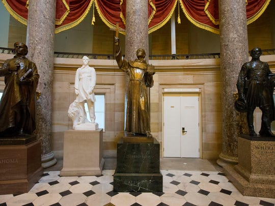 In this July 2, 2015, file photo, the statue of missionary Junipero Serra, center, is displayed in Statuary Hall, also known as the Old Hall of the House, on Capitol Hill in Washington. Public statues and live tributes to early Spanish conquerors who colonized the Southwest and portions of Florida are enduring an onslaught of criticism, as questions multiply about how to address the brutal treatment of Native Americans and activists draw ethical parallels to Confederate monuments and history.
