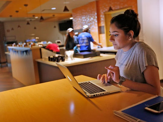 Alina Husain works on her computer in the coffee shop
