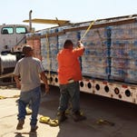 Tulare County workers tie down pallets of bottled drinking water onto a flatbed trailer at Sequoia Field Airport, north of Visalia, to transport it to East Porterville to be distributed among residents there.