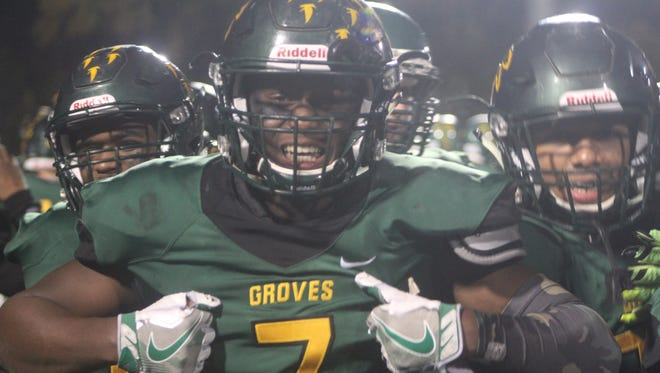Junior Chase Ford (7) and his Groves teammates celebrate their shutout victory over Brother Rice on Friday night.