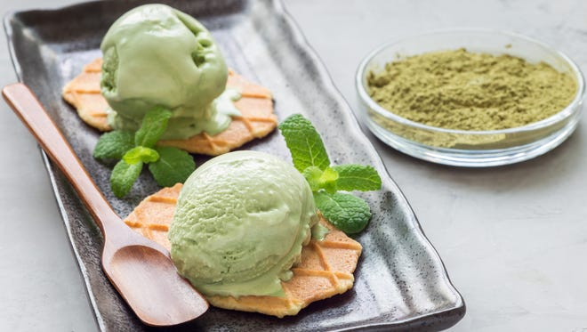 Matcha green tea ice cream balls served with waffles on black plate, horizontal, copy space