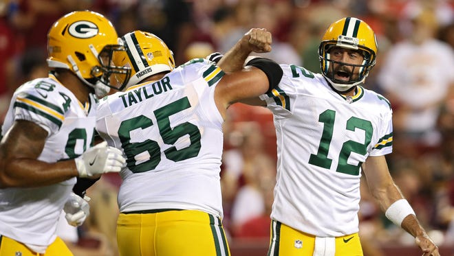 Packers QB Aaron Rodgers celebrates a touchdown pass with teammate Lane Taylor in the first half.