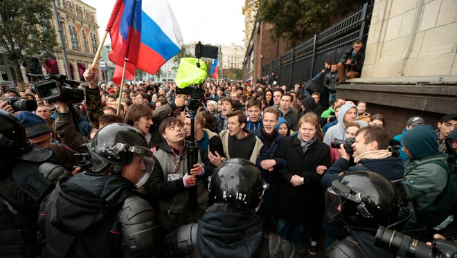 Riot police officers block protesters with Russian flag during a rally in Moscow, Russia, Oct. 7, 2017. Opposition leader Alexei Navalny has worked to organize protests in support of his presidential bid across Russia on President Vladimir Putin's 65th birthday.