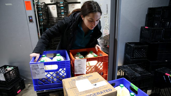 Carmelle Wasch, of Ohio Valley Food Connection, receives food from suppliers, Thursday, Jan. 18, 2018, in Newport, Ky. In the warehouse, farmers drop off their produce, which they packages and then supply to restaurants.