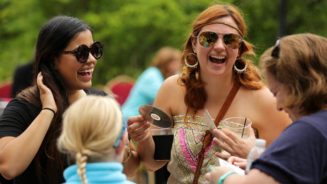 Gabby of Vic and Gab (left) talks with Amber Alcorn of Independence, Missouri and Sue Conway of Racine as musicians and fans take part in Mile of Music in downtown Appleton.