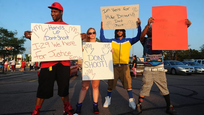 """The hands up, don't shoot"" protest at the corner of 41st Street and Minnesota Ave. in Sioux Falls on Tuesday, Aug. 19, 2014."