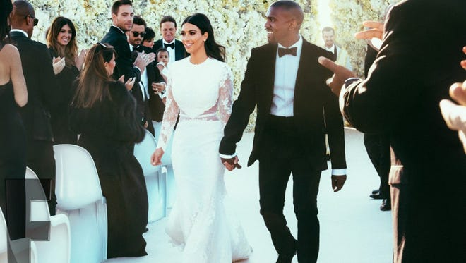 Kim Kardashian and Kanye West walk down the aisle at their wedding.