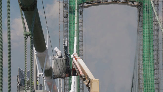 Joe Carlson spray paints the suspension cables of the Walt Whitman Bridge this summer. Corcon Inc. of Ohio is the contractor in charge of painting and steel plate replacement as it will be for a similar project to start on the Betsy Ross Bridge between Northeast Philadelphia and Pennsauken