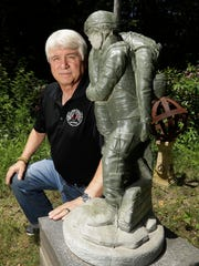 Former Army medic James McCloughan kneels next to a statue presented to him by a fellow soldier in South Haven, Mich. on June 9, 2017.
