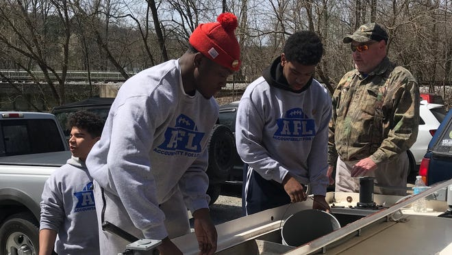 Members of York High's Accountable For Life program help stock trout with organizers from Hopewell Fish and Game Association.