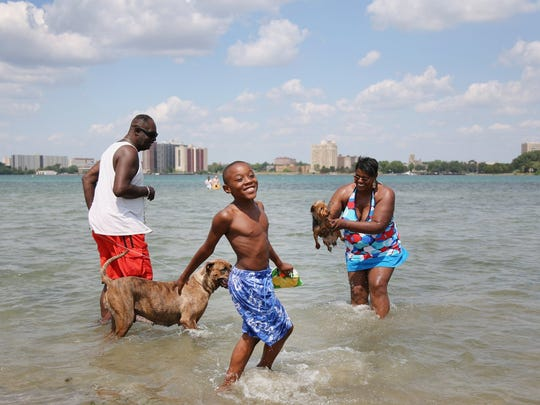 "Antonio Pewee, 8, center, cools down with his family, ""Trouble,"" an American bulldog; his father, James Wilson, left, and mother, Yolanda Gaylor, and her Yorkie, all of Detroit in the water at the beach on Belle Isle in Detroit on Tuesday July 17, 2012."