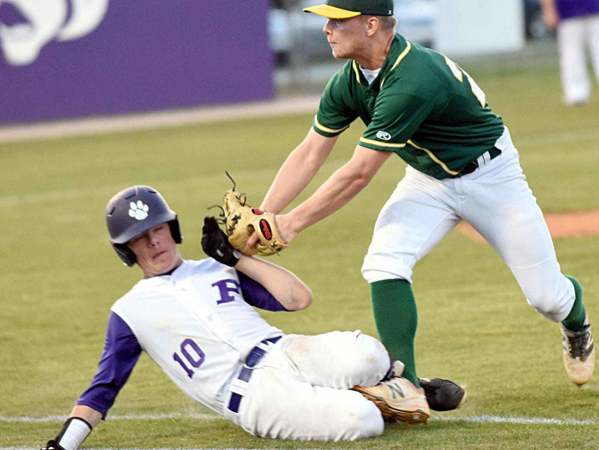 Gallatin High senior starting pitcher James Rockwell tags out Portland sophomore Logan Wilson during the first inning of Monday evening's 20-4 win for the Green Wave.