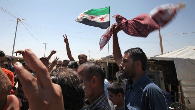 Syrian refugees call for an international military strike on the Syrian regime at camp, in Jordan on Wednesday.