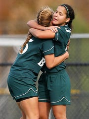 East Brunswick's Sydney Rosa, right, gets a hug from teammate Michelle Popuski, left, after scoring a goal in the second half against Old Bridge during the girls soccer GMC Tournament Final in South Brunswick, N.J. on Sunday, November 9, 2014. East Brunswick defeated Old Bridge 1-0.