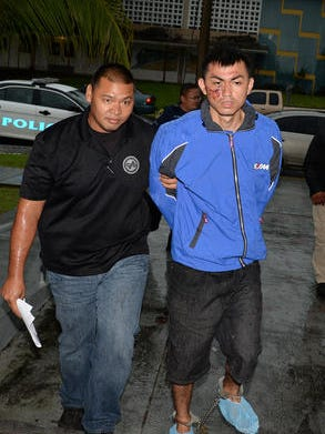John Anthony McCord Jr. is escorted to the Hagatna precinct upon his arrest in July 2014.