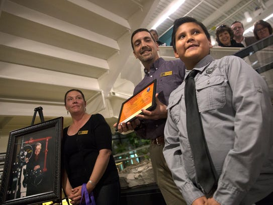 Dana Hawkins, left, an advisory committee member of the Sherman Dugan Museum, and John Burris, professor of geology at San Juan College, present a certificate to Valentino Levaldo for suggesting the name Mery for an oreodont fossil unveiled Wednesday at the Sherman Dugan Museum at San Juan College.