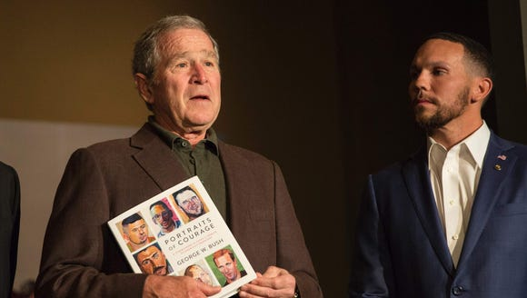 Former president George W. Bush holds up a copy of