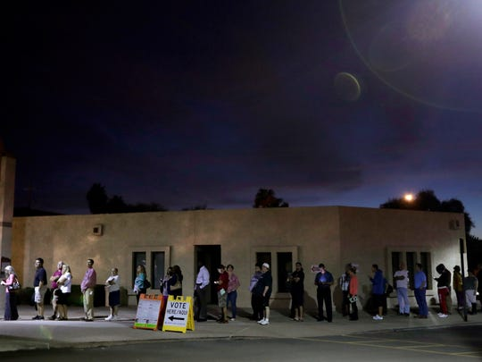 Voters wait for the polls to open at dawn Tuesday in