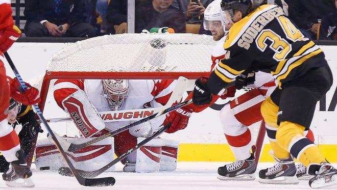 The net falls on Detroit Red Wings goalie Petr Mrazek as Riley Sheahan, center, defends Carl Soderberg (34) in Boston on Oct. 4, 2014.