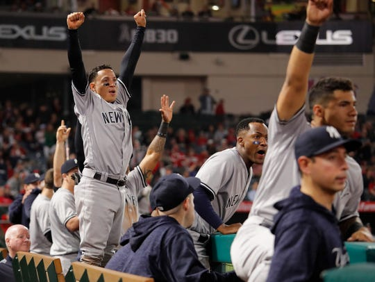 The New York Yankees players react to a home run by