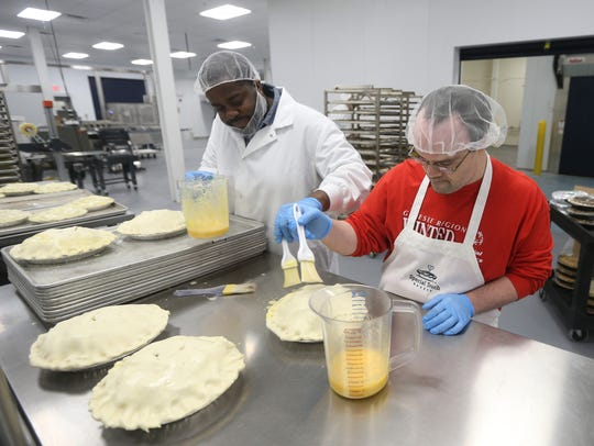 Tim Kelly applies an egg wash to an apple pie with