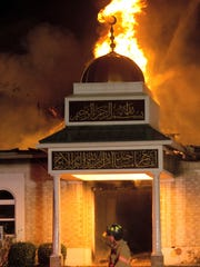 A firefighter walks in front of the Islamic Center of Victoria on Saturday, Jan. 28, 2017, in Victoria. The early-morning fire Saturday destroyed the mosque that was a target of hatred several years ago and experienced a burglary just a week ago.