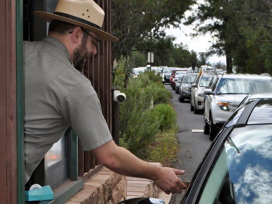 FILE--In this file photo taken Aug. 2, 2015, Nate Powell, an employee with Grand Canyon National Park, collects an entrance fee as traffic is backed up as vehicles arrive at an entrance gate at Grand Canyon National Park, Ariz. A new study concludes visitors may be steering clear of some U.S. national parks or cutting their visits short because of pollution.(Emery Cowan/Arizona Daily Sun via AP, file)