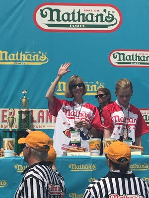 Montville Superintendent of Schools Rene Rovtar waving prior to Nathan's Hot Dog Eating Contest on Tuesday, July 4. Rovtar managed to consume eight wieners and rolls in 10 minutes.