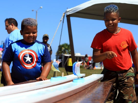 Sean Lester (left) and William Lester race boats Tuesday, July 4, 2017, in the Kids/Game Zone at the Mayor's Fourth of July Big Bang Celebration in Corpus Christi.