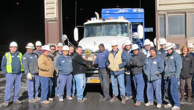 Wheelabrator Westchester employees join plant manager Brett Baker and operations manager Phil Schwer to present a gift basket to City Carting driver Mike McKenzie as he delivers the 20 millionth ton of trash to the energy-from-waste facility.
