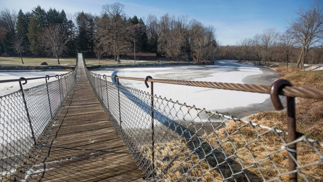The swinging bridge stretches over the icy Black River at the Croswell Park Sunday, Jan. 16, in Croswell.