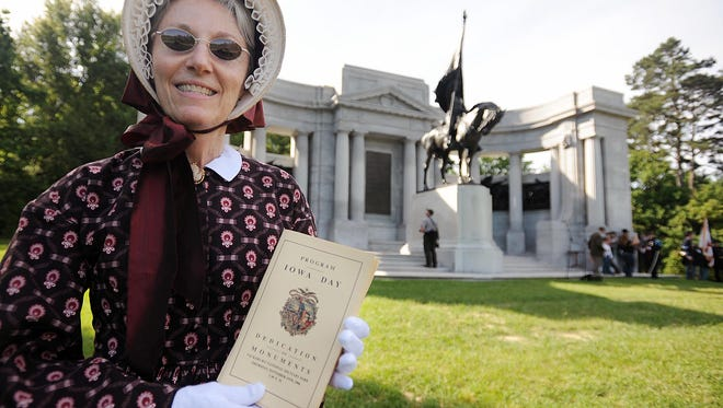 Dana Lamb, dressed in period clothing typical of the 1800s, shows a replica of the original program for the Iowa monument dedication ceremony held on November 15th 1906 at the Vicksburg National Military Park.
