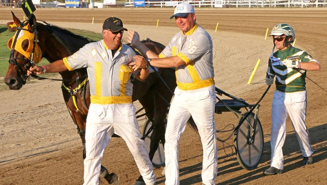 Trainers Mickey, left, and Ron Burke congratulate each other as driver Yannick Gingras holds the lines of Limelight Beach after winning the Little Brown Jug harness race at the Delaware County Fairgrounds on Sept. 18, 2014.