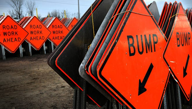 Road construction signs sit ready for use.