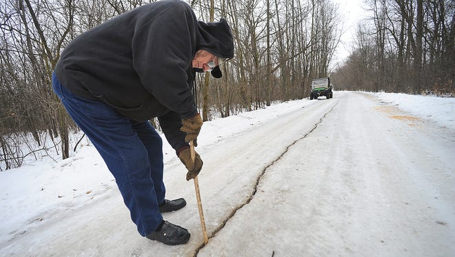 Dennis Olsen of Waupun measures a crack 10 inches deep caused by a frost quake in 2014.