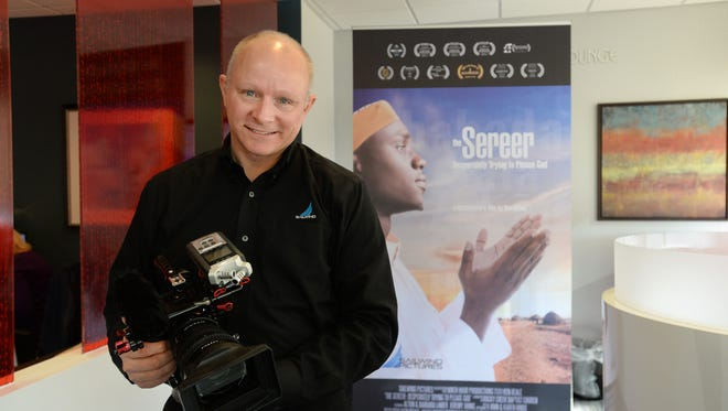Ken Beale of Sailwind Pictures stands near the poster for the documentary film that he wrote, produced and directed.