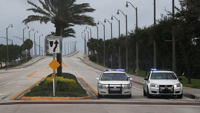 Police vehicles block the entrance to Hutchinson Island, Fla., as Hurricane Matthew approaches the area Thursday, Oct. 6, 2016 in Jupiter, Fla. A 58-year-old woman died of a heart attack early Friday, Oct. 7, 2016, after St. Lucie County suspended emergency services.
