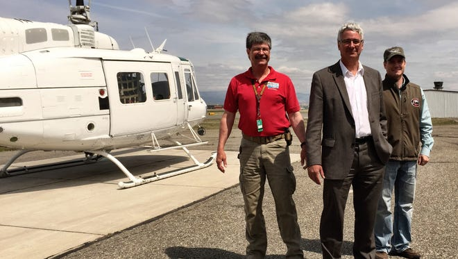 From left, safety pilot Randy Yaeger, DNRC Director John Tubbs and safety pilot Tal Williams look over helicopters preparing for the upcoming fire season.
