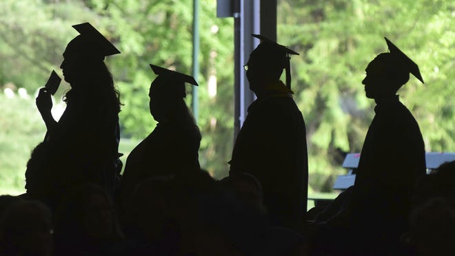 In this Friday, June 1, 2018, file photo, graduates are silhouetted against the green landscape as they line up to receive their diplomas at Berkshire Community College's commencement exercises at the Shed at Tanglewood in Lenox. Some lenders advertise their products as a way to pay for college, but these aren't technically student loans. For unsuspecting students, that could lead to unnecessarily high costs and a lack of consumer protection.
