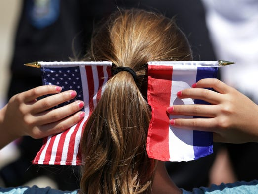 A girl holds American and Dutch flags in her hair during