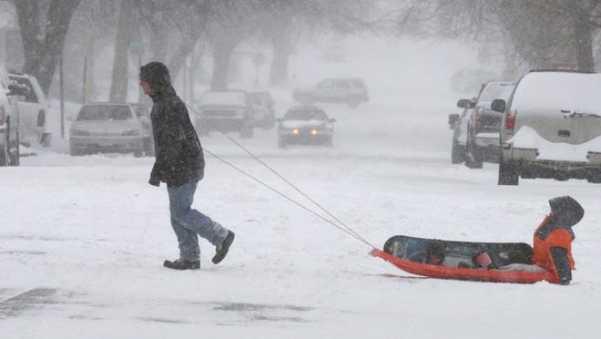 Alex Sepstead, 18, pulls his little brother Nevan, 10, both of Sheboygan, on N. 16th Street Sunday February 1, 2015 during blizzard-like conditions that hit Sheboygan.