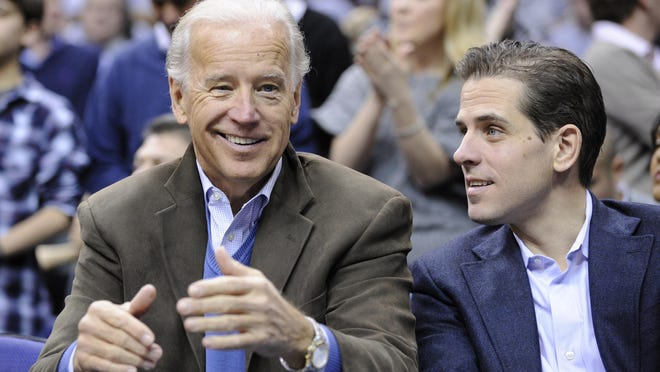 FILE - In this Jan. 30, 2010, file photo, Vice President Joe Biden, left, with his son Hunter, right, at the Duke Georgetown NCAA college basketball game in Washington.  Since the early days of the United States, leading politicians have had to contend with awkward problems posed by their family members. Joe Biden is the latest prominent politician to navigate this tricky terrain.