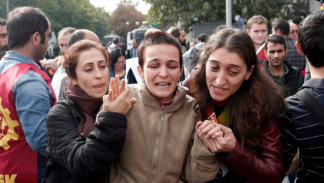 A woman mourns for victims as her friends comfort her during a demonstration one day after multiple explosions ahead of a rally, in Ankara, Turkey, October 11, 2015.