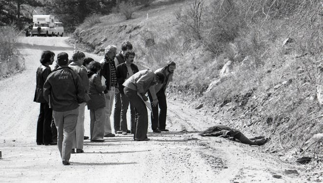 Larimer County sheriff's investigators are shown with one of the victims in the Mata murders in this April 29, 1978, archive photo.