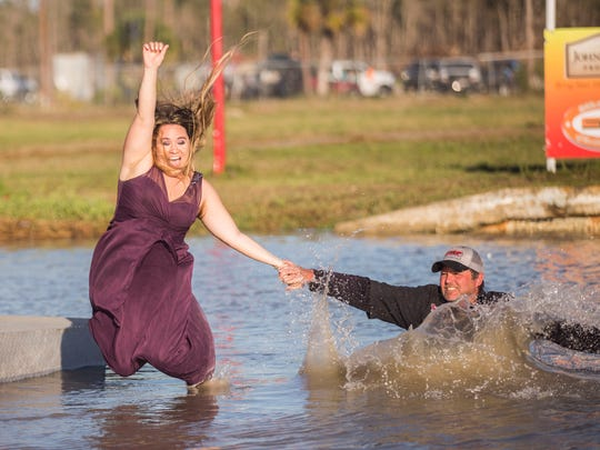 Swamp Buggy Queen Erica Flesher jumps in the swamp