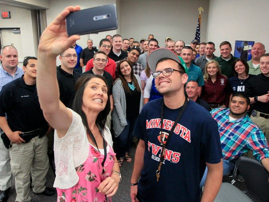 Conner Jackson, right, who has been diagnosed with ADHD, bipolar disorder and schizophrenia, and his Gateway supervisor take a selfie with a group of law enforcement officials following a talk he gave at a crisis intervention training course at the Independent Living Resource Center on Wednesday, June 21, 2017 in west Wichita, Kan. (Fernando Salazar/Wichita Eagle/TNS)