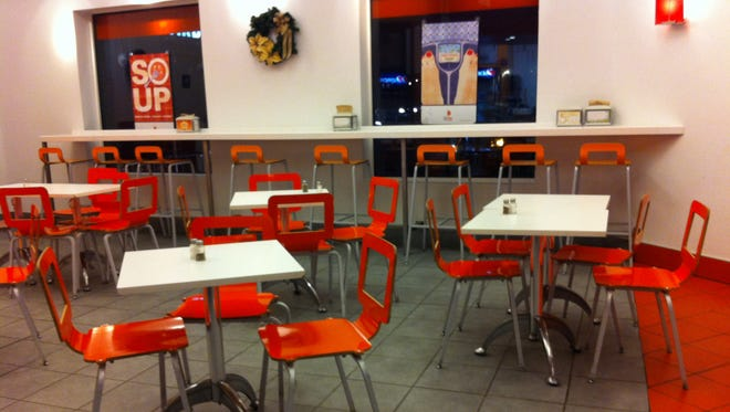 Half Moon Creative Salads is at 2900 Monroe Ave. in Clover Commons, Brighton. The small dining space is spare and modern, with gray tile floors, white walls, white tables and bright orange chairs.