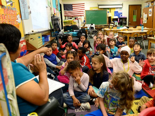 Children in Soledad Ramirez Heiler's kindergarten class learn about compound words by clapping their hands together and pulling them apart Wednesday, September 30, 2015, at North Elementary in Lansing. 50% of North's students are English learners and come from 27 countries. Schools like North stand ready to accept incoming Syrian refugees if and when the resettle in the Lansing area.